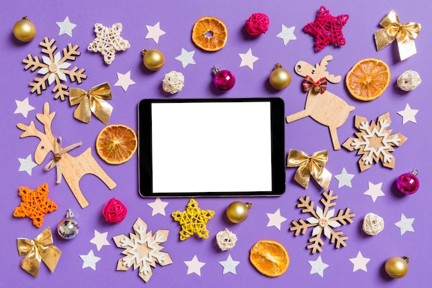 Top view of digital tablet surrounded with new year toys and decorations on purple.