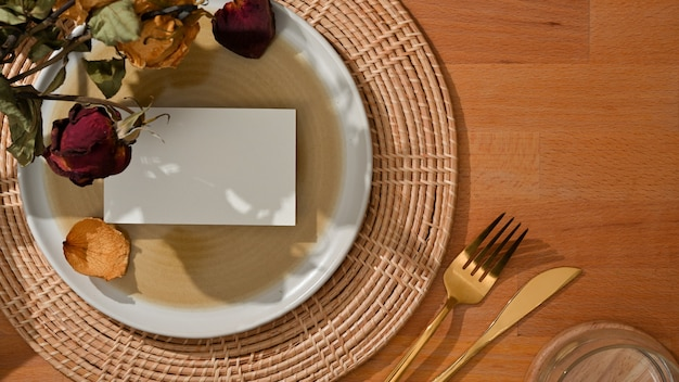 Top view of dining set with mock up name card on plate and brass fork, table knife and flower decorated on the table