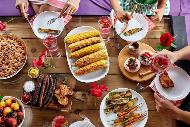 Top view over a dining table, decorated with flowers, with tableware and food. backyard picnic with friends or neighbors, family dinner.