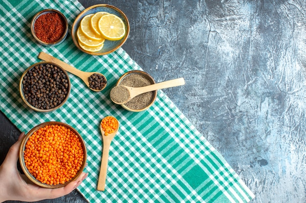 Top view of dinner background with different spices hand holding yellow pea on green stripped towel on dark table