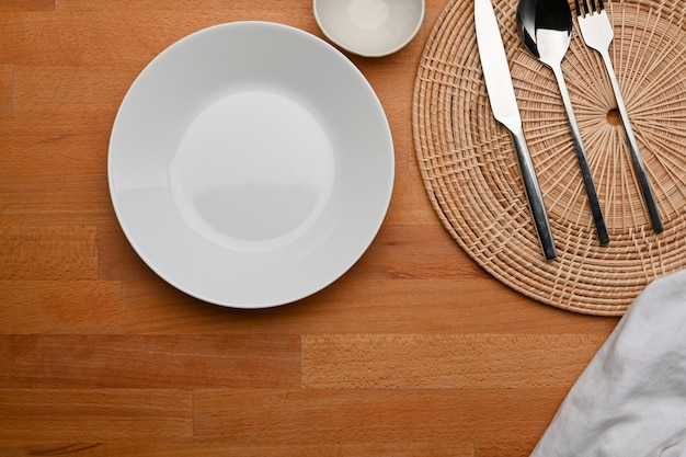 Top view of dinning table with mock up ceramic plate cutlery place mat and copy space