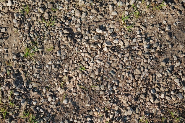Top view of dirt road fragment. dry land with stones. abstract natural textured background.