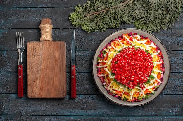 トップビューの皿とトウヒの枝まな板の横にあるクリスマスの皿フォークナイフと暗いテーブルのトウヒの枝