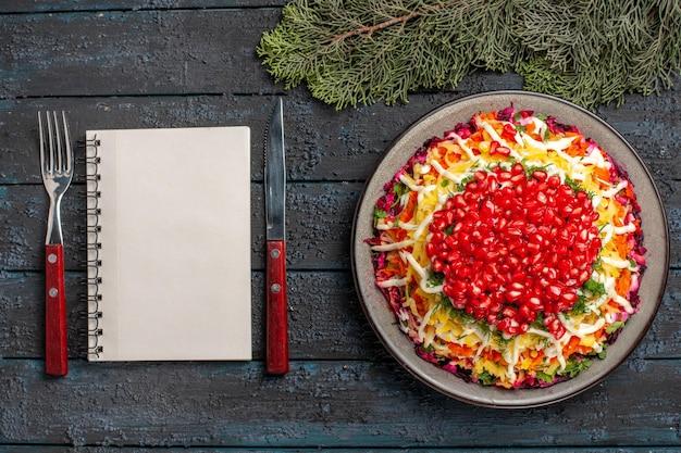 Вид сверху блюдо и еловые ветки новогоднее блюдо рядом с вилкой, белый блокнот, нож и еловые ветки на темном столе