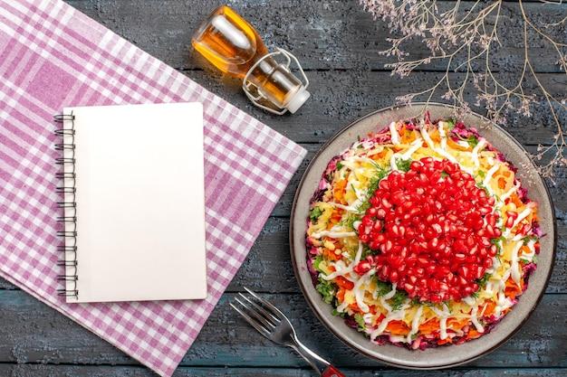 Вид сверху блюдо и скатерть блюдо из гранатового морковного картофеля рядом с бутылкой масляной вилки ветки деревьев и блокнот на розово-белой клетчатой скатерти