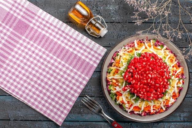 油の木の枝とピンクホワイトの市松模様のテーブルクロスのボトルの横にあるザクロにんじんポテトの上面図とテーブルクロスの皿