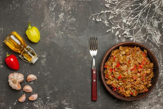 Vista dall'alto piatto di fagioli aglio peperoni olio in bottiglia e piatto di fagiolini e pomodori sul tavolo