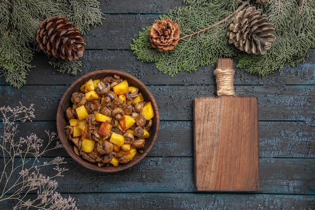Top view dish and board bowl of potatoes and mushrooms next to the cut board under the spruce branches with cones