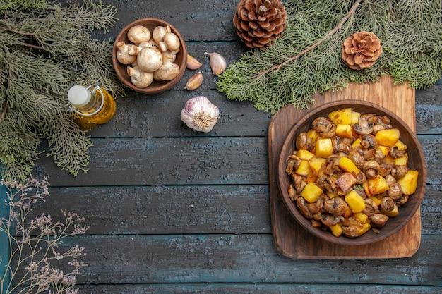 Vista dall'alto piatto e rami piatto di funghi con patate sul tagliere accanto all'olio in bottiglia aglio ciotola di funghi e rami con coni
