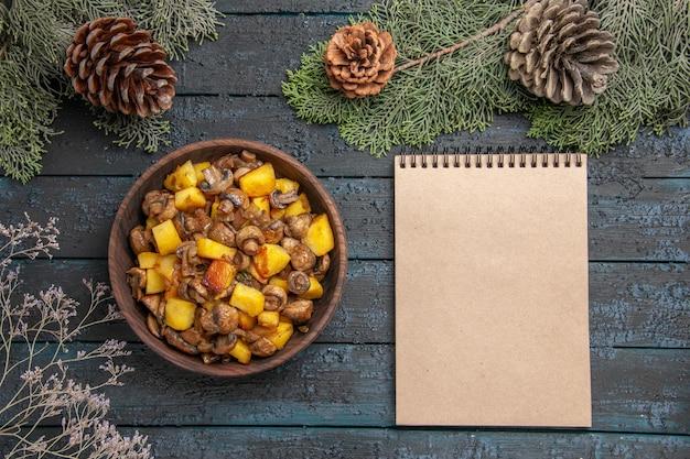 Piatto vista dall'alto e ciotola per notebook di patate e funghi accanto al notebook sotto i rami di abete con coni