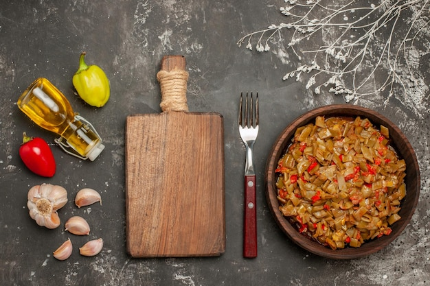 フォークまな板の横にあるボトルに入った豆ガーリックピーマンオイルの上面図とテーブル上のインゲンとトマトのプレート