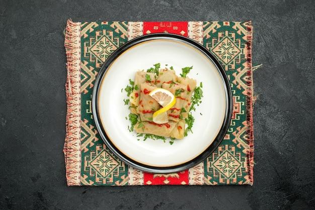 어두운 탁자 중앙에 있는 여러 가지 빛깔의 체크무늬 식탁보에 채워진 배추를 식욕을 돋우는 식탁보 위의 탑 뷰 접시
