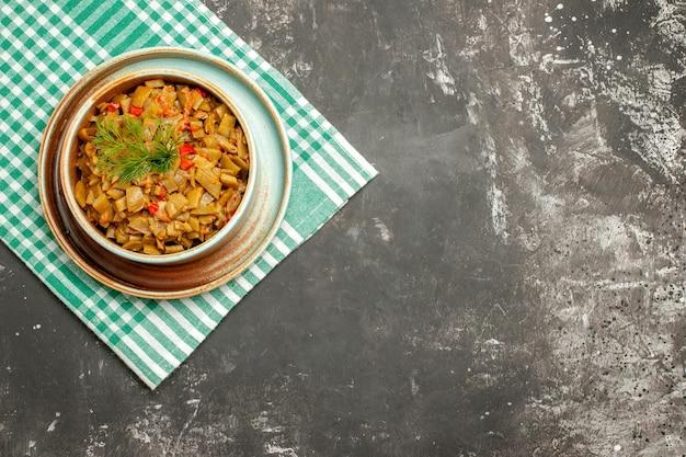 어두운 탁자의 왼쪽에 있는 체크무늬 식탁보에 있는 보드에 토마토와 함께 식욕을 돋우는 녹색 콩의 식탁보 접시에 있는 탑 뷰 접시
