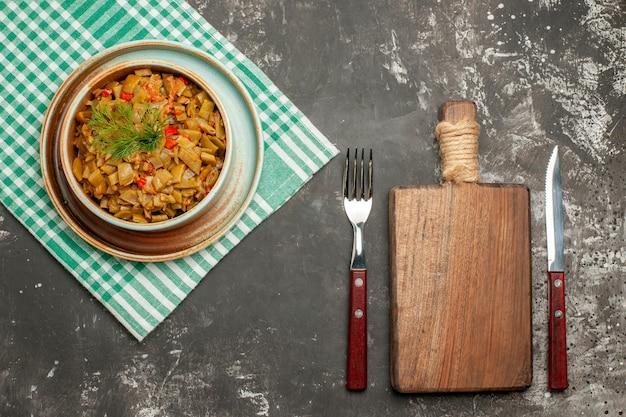 テーブルクロスの上面図木製まな板フォークナイフと暗いテーブルの市松模様のテーブルクロスにトマトと食欲をそそるサヤインゲンのプレート