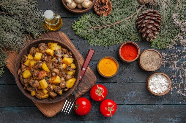 Top view dish and spices dish of potatoes and mushrooms on the cutting board next to the fork three tomatoes and colorful spices under oil bowl of white mushrooms and spruce branches