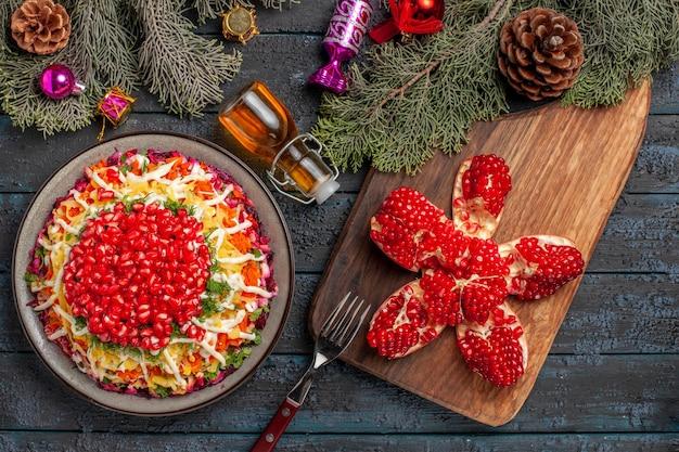 Piatto vista dall'alto e piatto di spezie con melograno accanto alla bottiglia di olio di melograno forchetta sul tagliere e rami di albero con coni e giocattoli dell'albero di natale