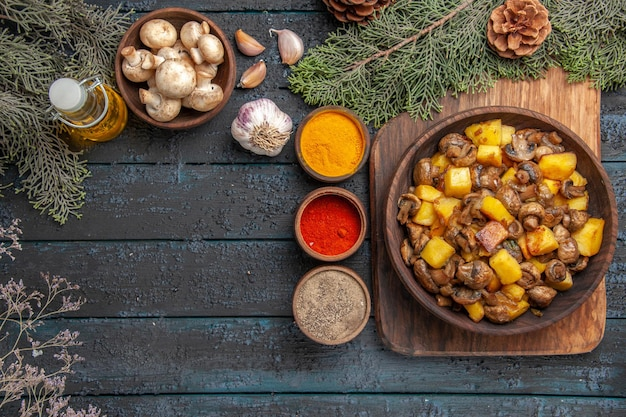 Top view dish and spices plate of mushrooms and potatoes on cutting board next to colorful spices oil in bottle garlic bowl of mushrooms under branches with cones