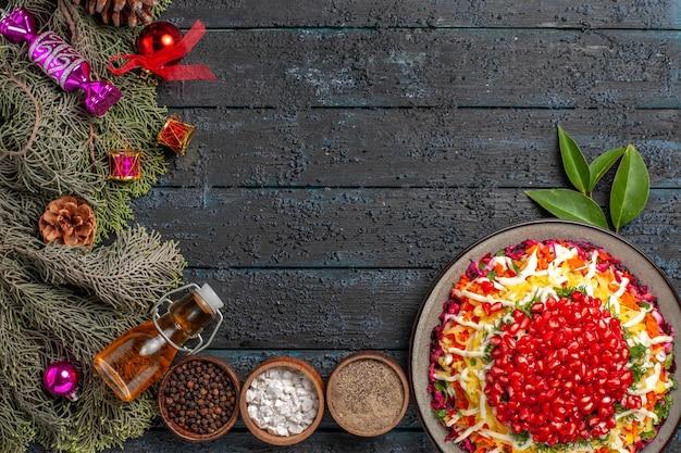 Piatto vista dall'alto e rami di abete appetitoso piatto di natale con bottiglia di olio e spezie accanto ai rami di abete con coni