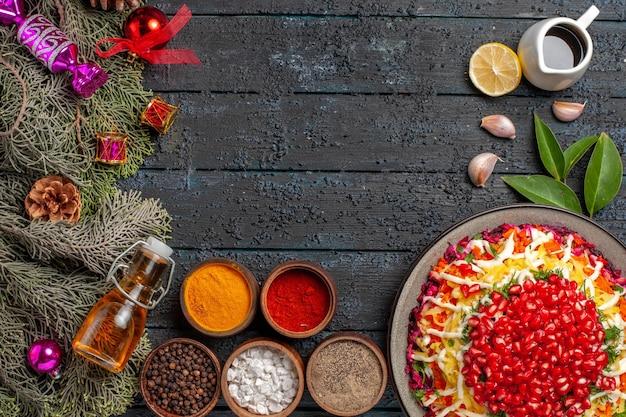 Piatto vista dall'alto e rami di abete appetitoso piatto di natale con bottiglia di olio al limone e spezie accanto ai rami di abete con coni e aglio