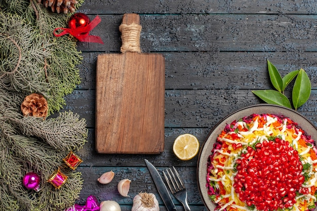 Top view dish and spruce branches appetizing christmas dish with lemon garlic next to the cutting board fork knife and spruce branches with cones