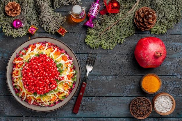 Piatto vista dall'alto con piatto di melograni con semi di melograno accanto alla bottiglia di olio spezie forchetta rami di abete con coni e giocattoli per alberi