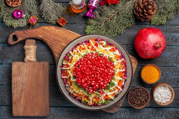 Piatto vista dall'alto con piatto di melograni con semi di melograno accanto al tagliere olio spezie rami di abete con coni e giocattoli per alberi