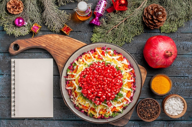Piatto vista dall'alto con piatto di melograni con semi di melograno accanto al quaderno bianco olio spezie rami di abete con coni e giocattoli ad albero