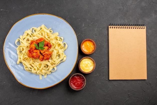 Вид сверху блюдо с соусами аппетитная паста с подливкой и мясом в тарелке рядом с кремовой записной книжкой три вида соусов на темном столе