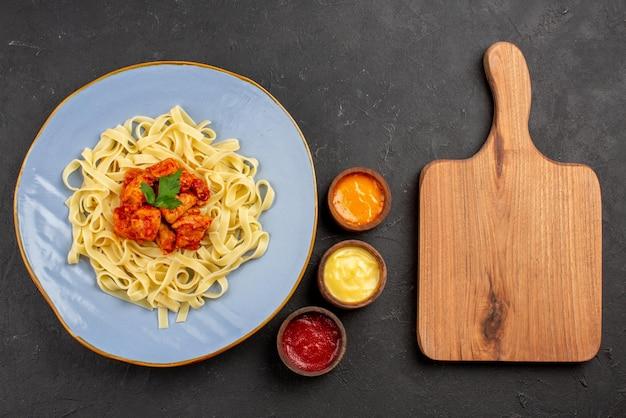 Вид сверху блюдо с соусами аппетитная паста с подливкой и мясом в тарелке рядом с деревянной разделочной доской и тремя видами соусов на темном столе