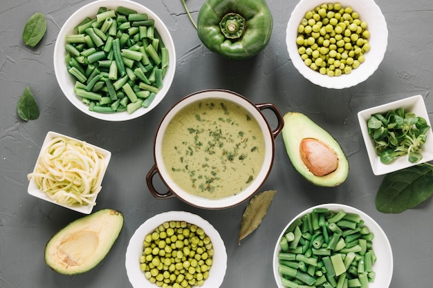 Top view of dishes with green peas and avocado