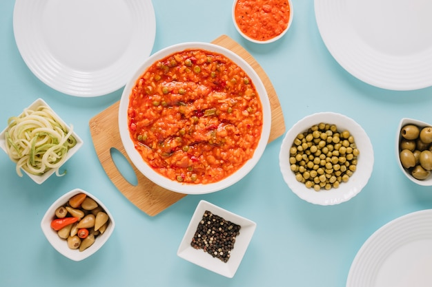 Top view of dishes with olives and hot peppers