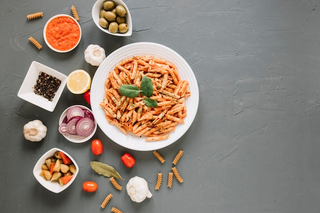 Top view of dishes with pasta and pepper
