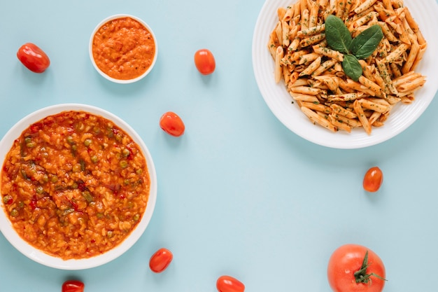 Top view of dishes with pasta and tomatoes