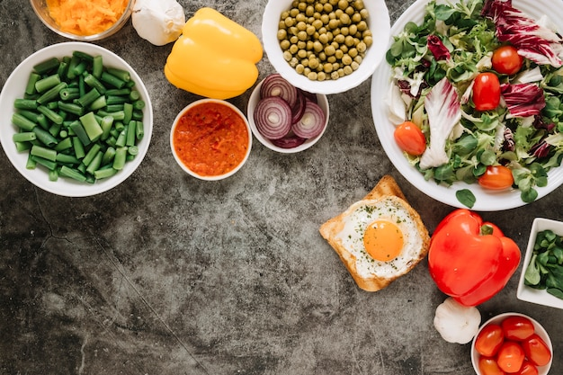 Top view of dishes with salad and fried egg on toast