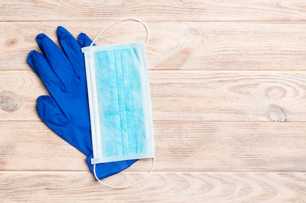 Top view of disposable medical mask and nitrile gloves on wooden wall. personal protection concept with copy space
