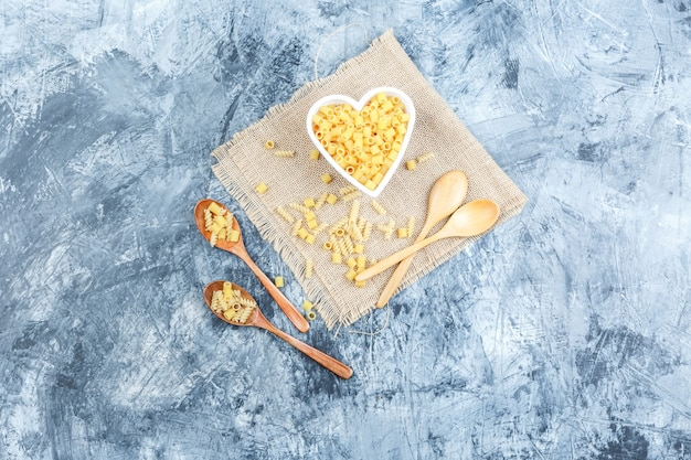 Top view ditalini pasta in bowl with wooden spoons on plaster and piece of sack background. horizontal