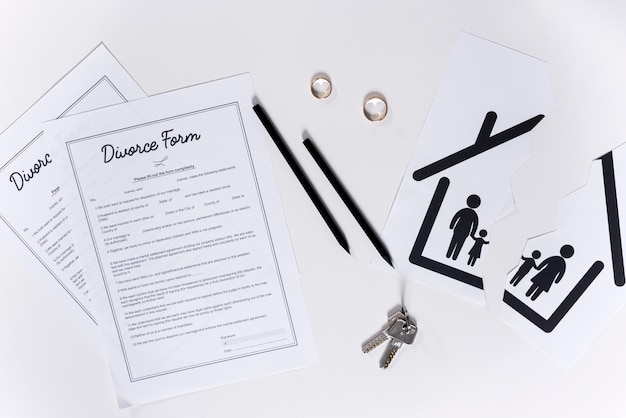 Top view divorce forms with house keys and wedding rings
