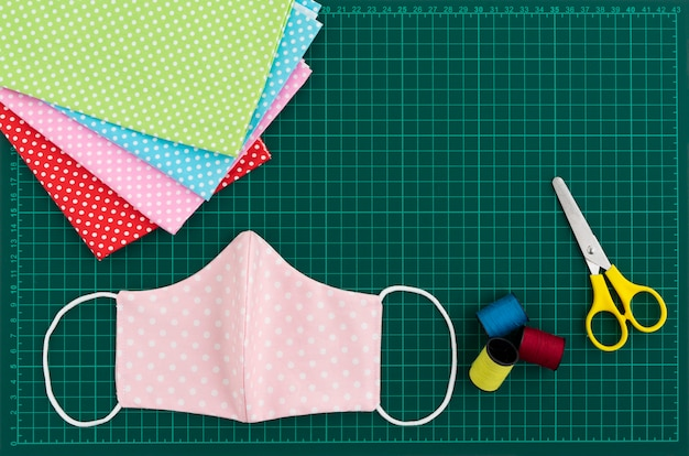 Top view of diy fabric cotton face mask on green cutting mat