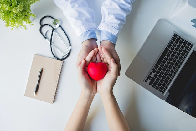 Вид сверху . руки доктора и пациента держа красное сердце на белом столе