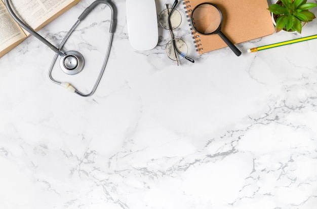 Top view of doctor desk marble table with stethoscope