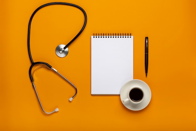 Top view of doctor desk table with stethoscope, coffee and blank paper on clipboard with pen. top view with copy space, flat lay