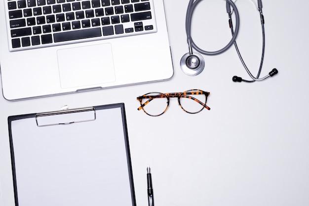 La vista dall'alto del desktop del medico con lo stetoscopio, gli appunti con la maschera medica e il computer portatile