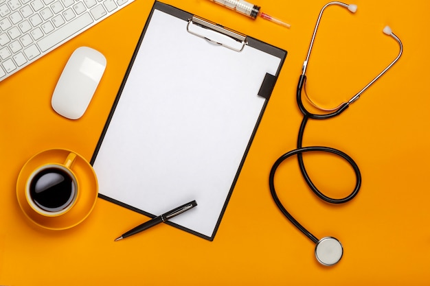 Top view of a doctor's table with notepad and pen stethoscope, keyboard, prescription and pills, a cup of coffee on a yellow background