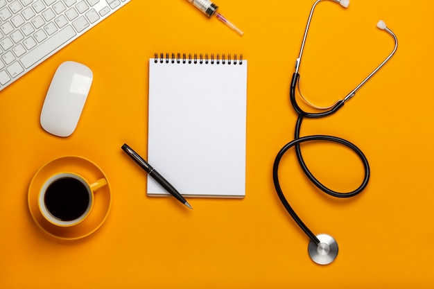 Top view of a doctor's table with notepad and pen stethoscope