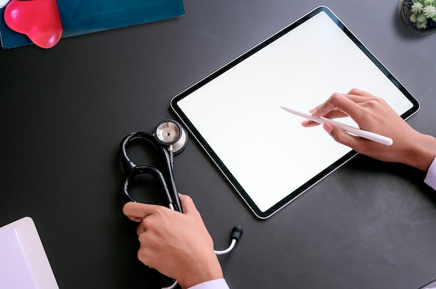 Top view of doctor working with digital tablet.