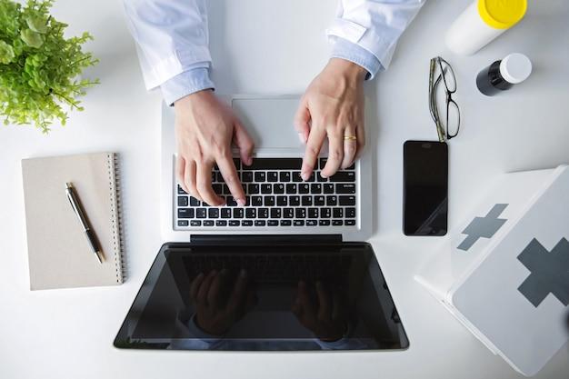 Рука top view.doctor работая с портативным компьютером в медицинском офисе места для работы как концепция