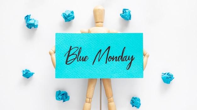 Vista dall'alto della bambola che tiene il segno blu del lunedì