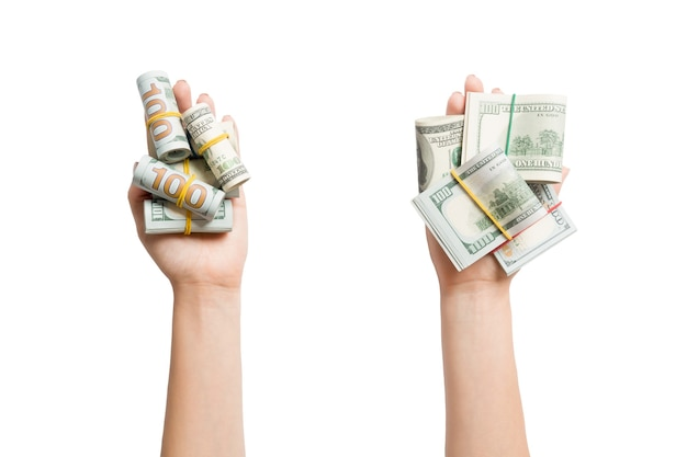 Top view of dollar bills in tubes in female hands on white isolated surface