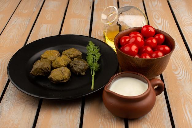 Vista dall'alto dolma con yogurt olio d'oliva e pomodori rossi sul pavimento di legno