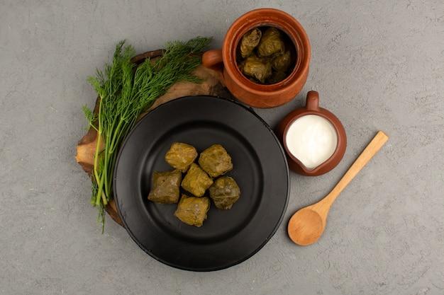 Вид сверху зеленый долма с мясным фаршем внутри черной тарелки вместе с йогуртом на сером полу